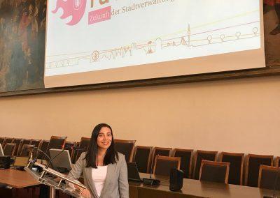 Nidan Tura steht am Rednerpult kurz vor Ihrer Präsentation