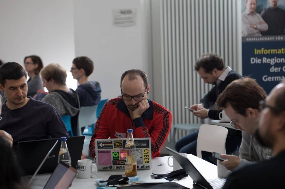 Teilnehmer hacken geimeinsam in Gruppen